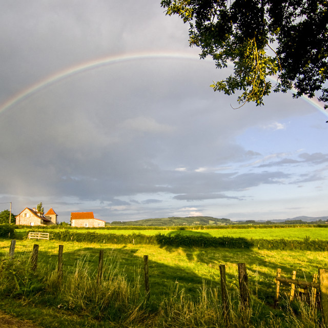 """Full rainbow with setting sun"" stock image"