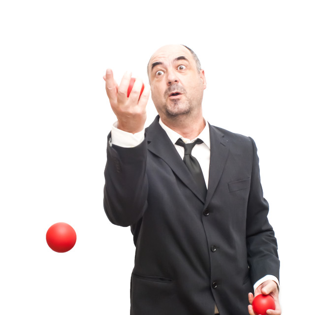"""Businessman that is juggling with a red balls"" stock image"