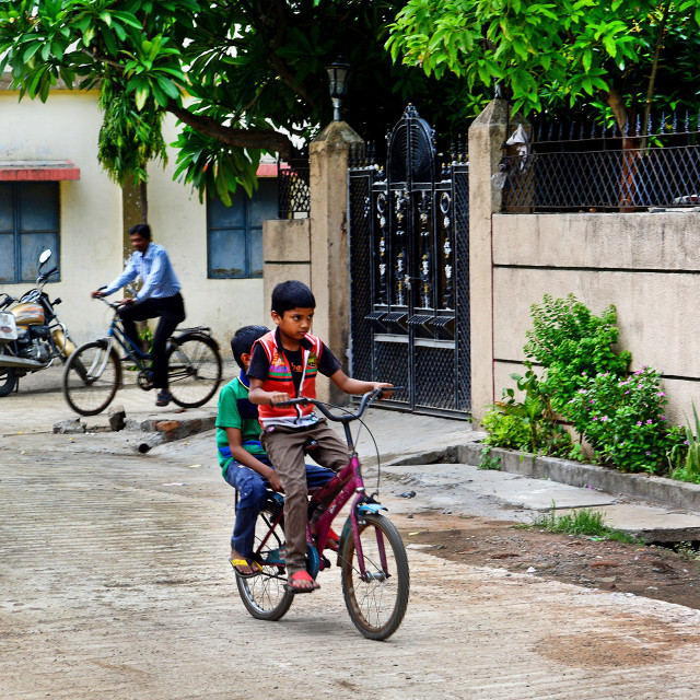 """Indian kids enjoying bicycle ride."" stock image"