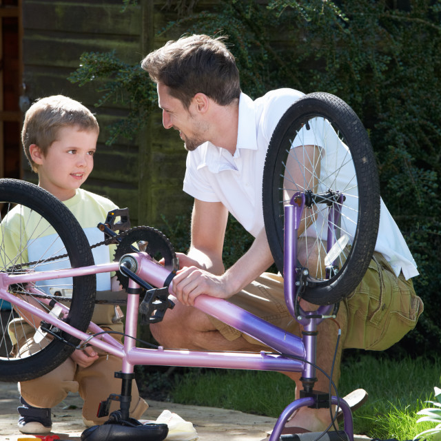 """Father And Son Mending Bike Together"" stock image"