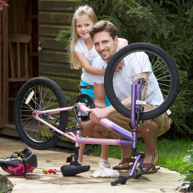 """Father And Daughter Mending Bike Together"" stock image"