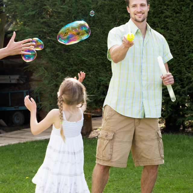 """""""Father And Daughter Playing With Bubbles In Garden"""" stock image"""