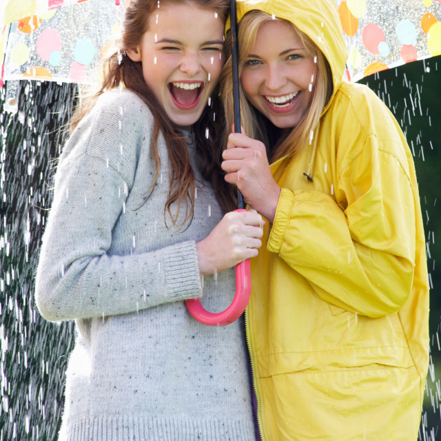 """Two Teenage Girl Sheltering From Rain Beneath Umbrella"" stock image"