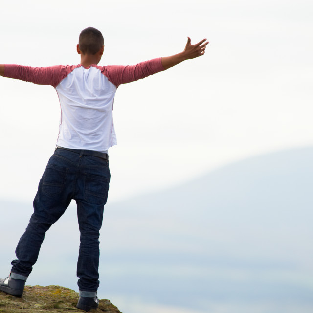 """""""Young Man Standing On Rock With Outstretched Arms"""" stock image"""