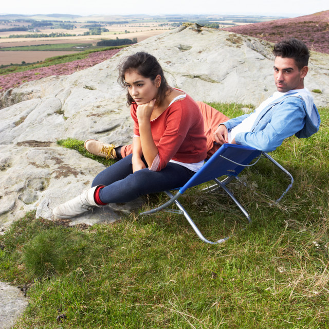 """""""Young Couple Sitting In Chairs On Camping Trip"""" stock image"""
