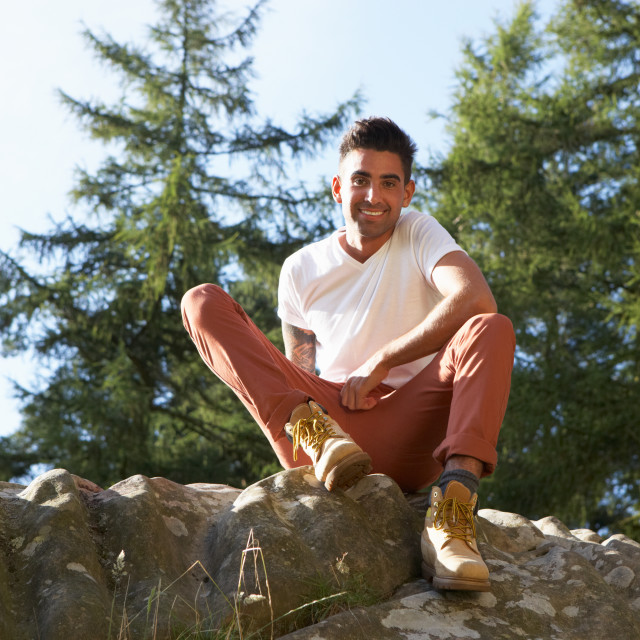 """""""Portrait Of Young Man Sitting On Rock"""" stock image"""