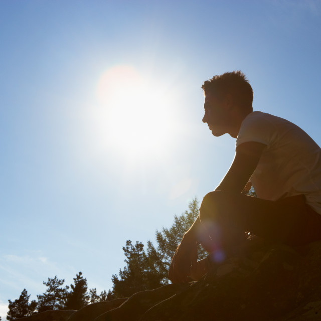 """""""Silhouette Of Young Man Sitting On Rock"""" stock image"""