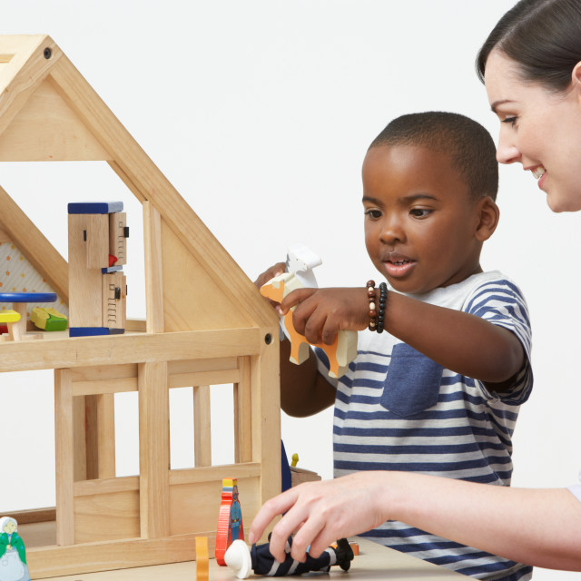 """""""Pre-School Teacher And Pupil Playing With Wooden House"""" stock image"""