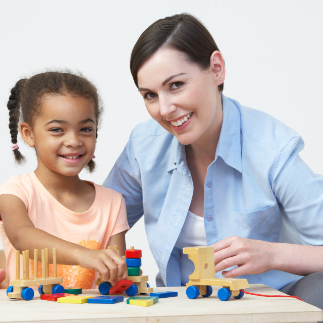 """""""Teacher And Pre-School Pupil Playing With Wooden House"""" stock image"""