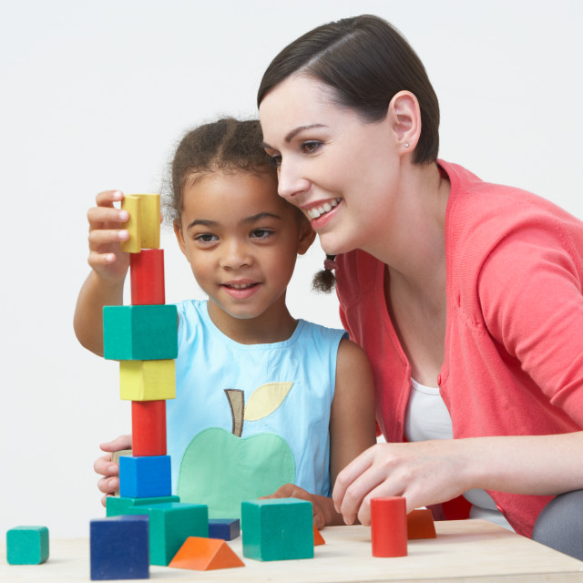 """""""Teacher And Pre-School Pupil Playing With Wooden Blocks"""" stock image"""