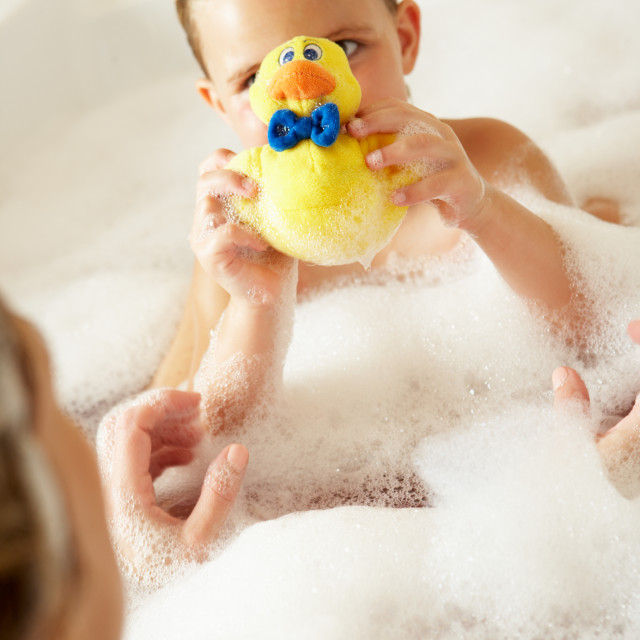 """""""Mother And Daughter Relaxing In Bubble Filled Bath"""" stock image"""