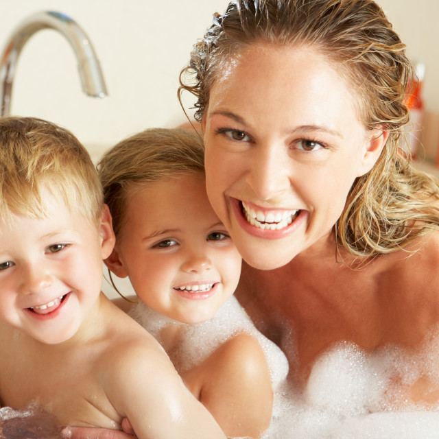 """""""Mother With Children Relaxing In Bubble Filled Bath"""" stock image"""