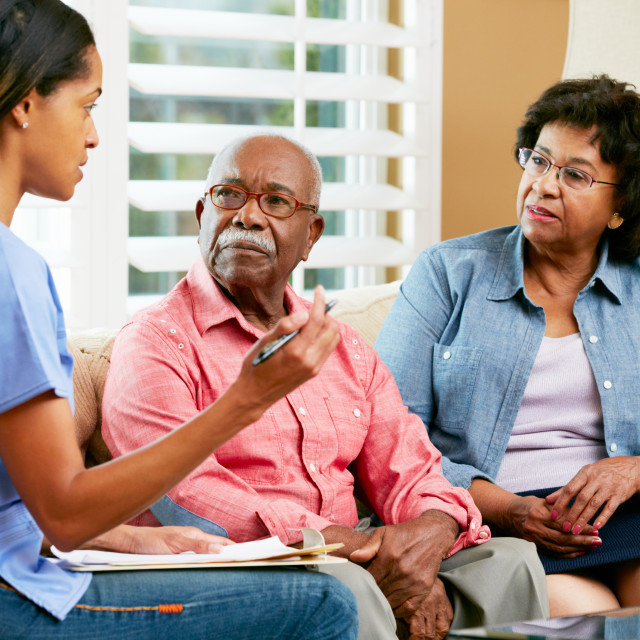 """""""Nurse Making Notes During Home Visit With Senior Couple"""" stock image"""