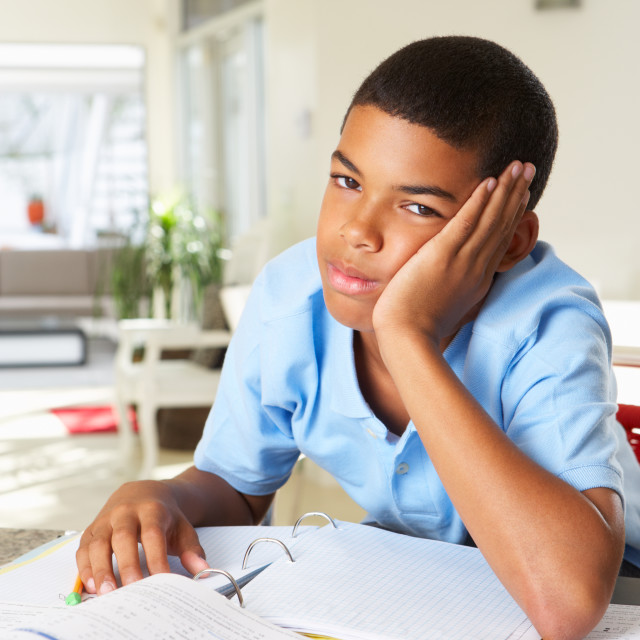 """""""Fed Up Boy Doing Homework In Kitchen"""" stock image"""