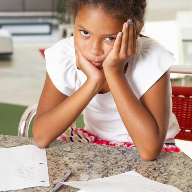 """Fed Up Girl Doing Homework In Kitchen"" stock image"