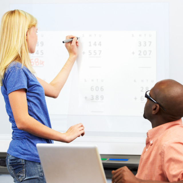 """Female Student Writing Answer On Whiteboard"" stock image"