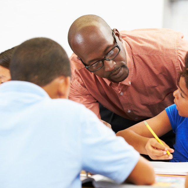 """""""Teacher Helping Pupils Studying At Desks In Classroom"""" stock image"""
