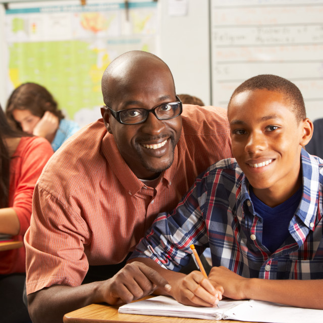 """""""Teacher Helping Male Pupil Studying At Desk In Classroom"""" stock image"""