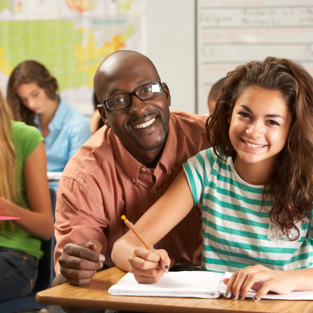 """""""Teacher Helping Female Pupil Studying At Desk In Classroom"""" stock image"""