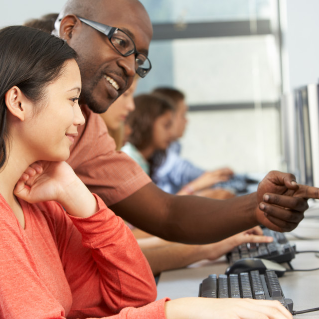 """""""Teacher Helping Students Working At Computers In Classroom"""" stock image"""