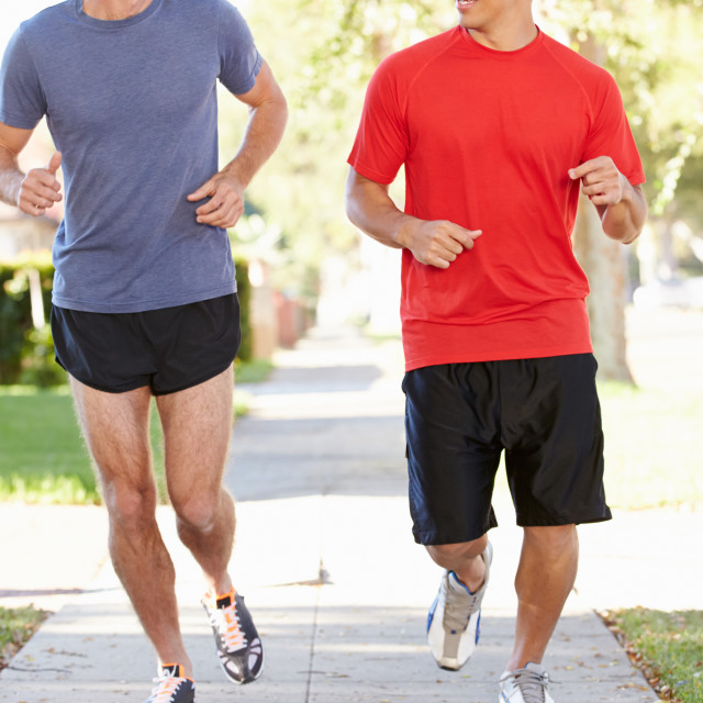 """""""Two Male Runners Exercising On Suburban Street"""" stock image"""