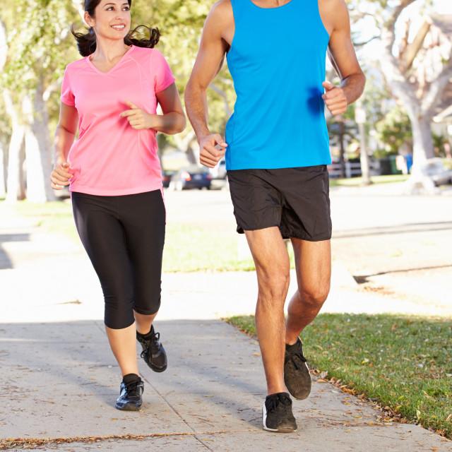 """""""Couple Running On Suburban Street"""" stock image"""