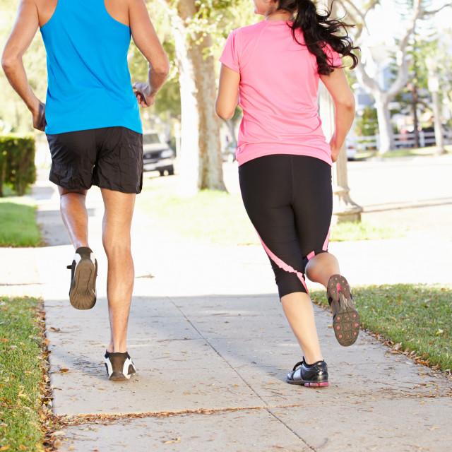 """Rear View Of Couple Running On Suburban Street"" stock image"