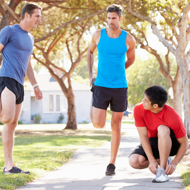 """""""Group Of Male Runners Warming Up Before Run"""" stock image"""