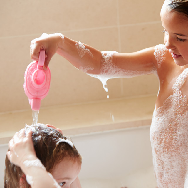 """""""Two Girls Sharing Bubble Bath And Washing Hair"""" stock image"""