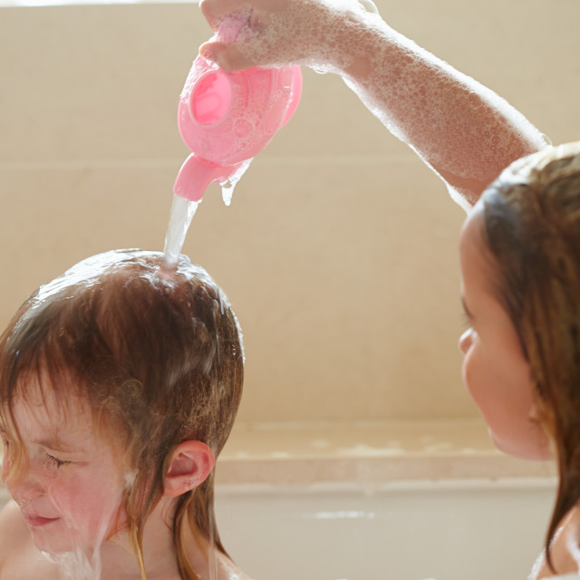 """Two Girls Sharing Bubble Bath And Washing Hair"" stock image"