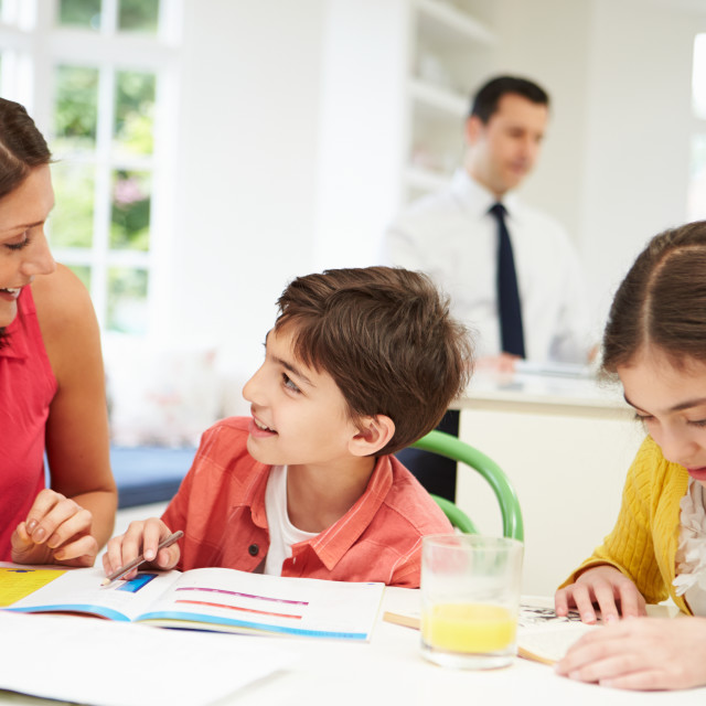 """Mum Helps Children With Homework As Dad Works In Background"" stock image"