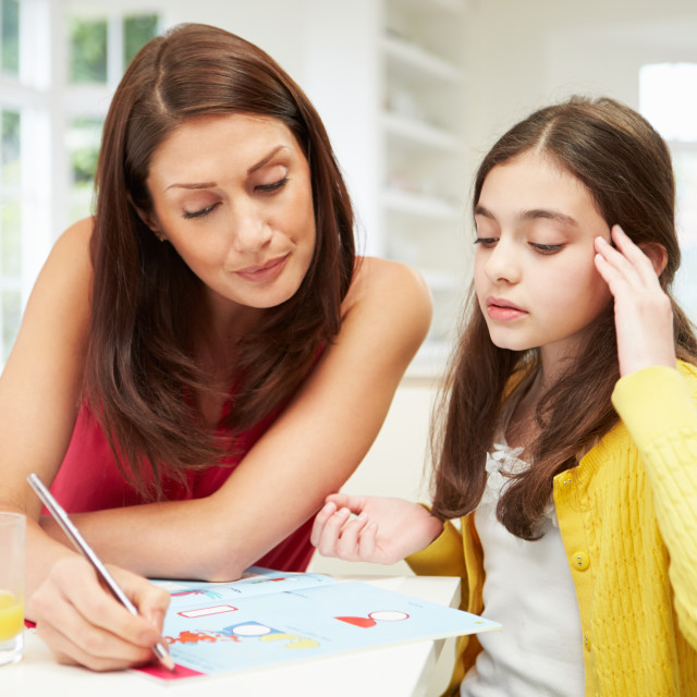 """Mother Helping Daughter Struggling With Homework"" stock image"