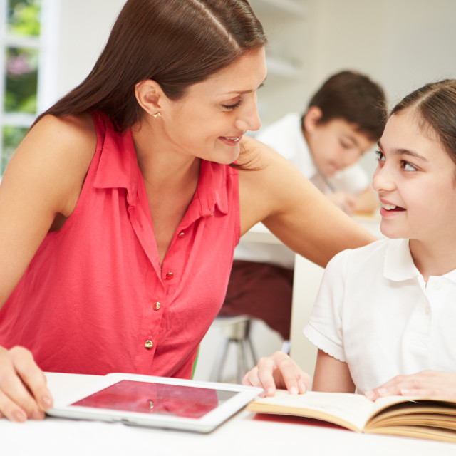 """Mother Helping Daughter With Homework Using Digital Tablet"" stock image"