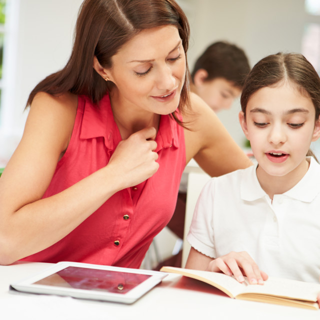 """""""Mother Helping Daughter With Homework Using Digital Tablet"""" stock image"""