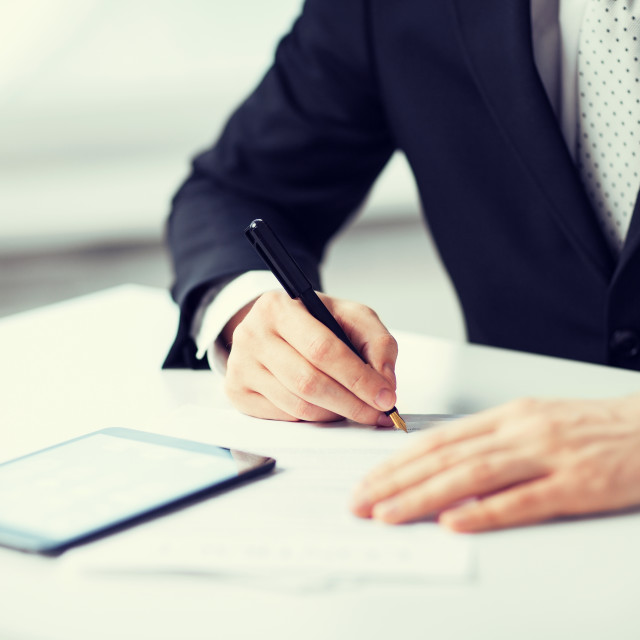 """""""man with tablet pc signing paper"""" stock image"""