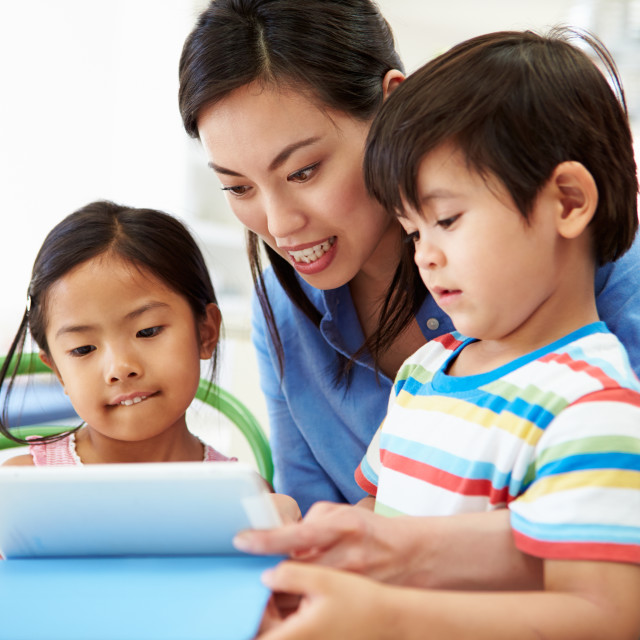 """Mother Helping Children With Homework Using Digital Tablet"" stock image"