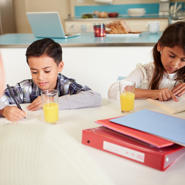 """Mother Helping Children With Homework At Table"" stock image"