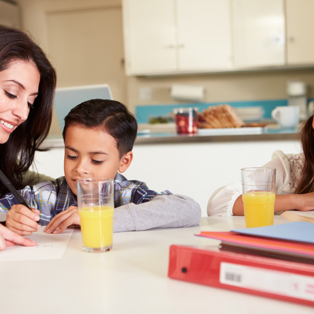 """""""Mother Helping Children With Homework At Table"""" stock image"""