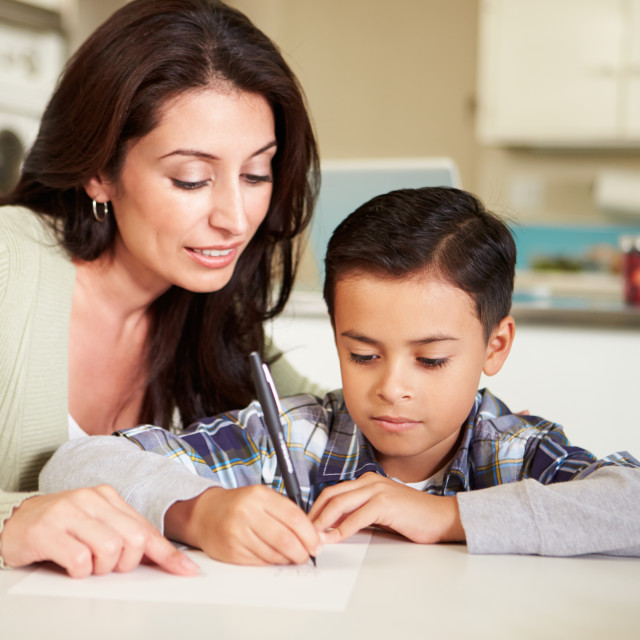 """Hispanic Mother Helping Son With Homework At Table"" stock image"