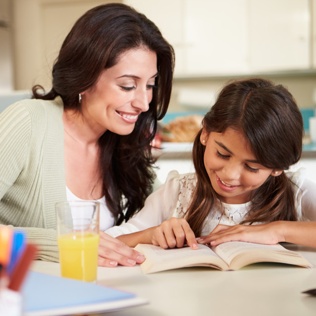"""Mother Helping Daughter With Reading Homework At Table"" stock image"