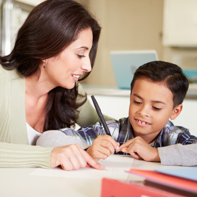 """""""Hispanic Mother Helping Son With Homework At Table"""" stock image"""