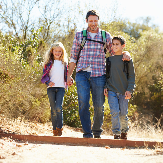 """""""Father And Children Hiking In Countryside Wearing Backpacks"""" stock image"""