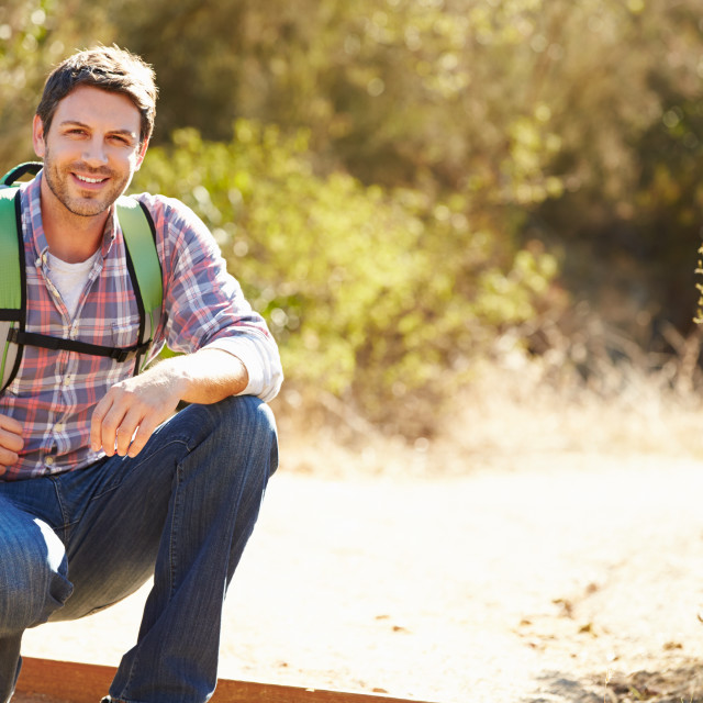 """""""Portrait Of Man Hiking In Countryside Wearing Backpack"""" stock image"""