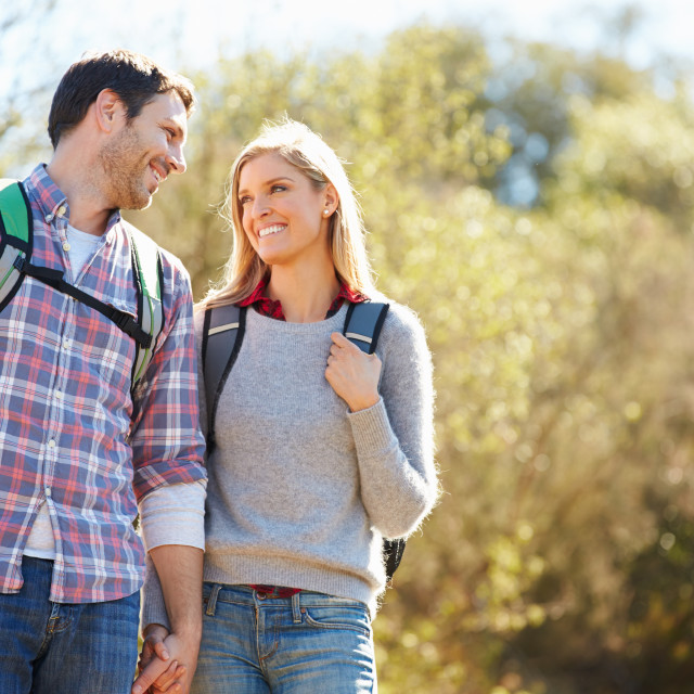 """""""Couple Hiking In Countryside Wearing Backpacks"""" stock image"""