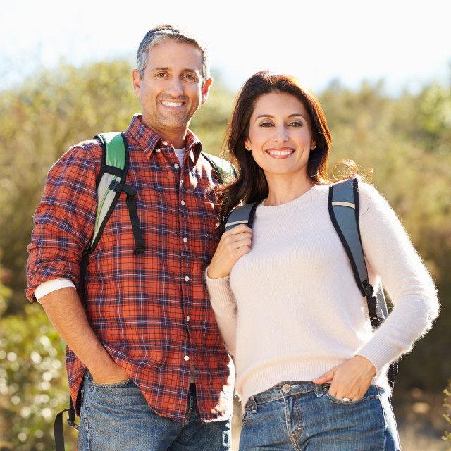 """""""Portrait Of Couple Hiking In Countryside Wearing Backpacks"""" stock image"""