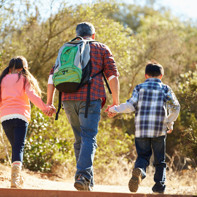 """""""Rear View Of Father And Children Hiking In Countryside"""" stock image"""