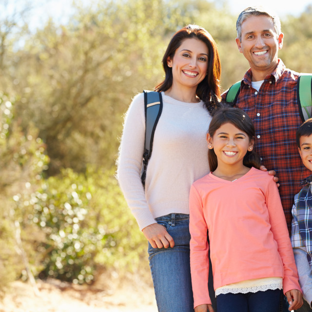 """""""Portrait Of Family Hiking In Countryside Wearing Backpacks"""" stock image"""