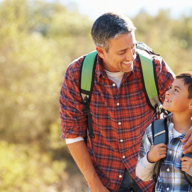 """""""Father And Son Hiking In Countryside Wearing Backpacks"""" stock image"""