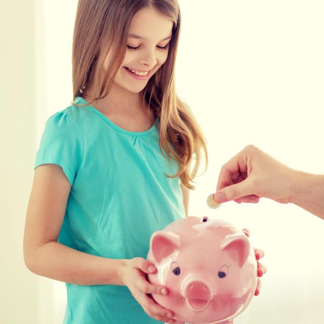 """""""smiling little girl holding piggy bank"""" stock image"""