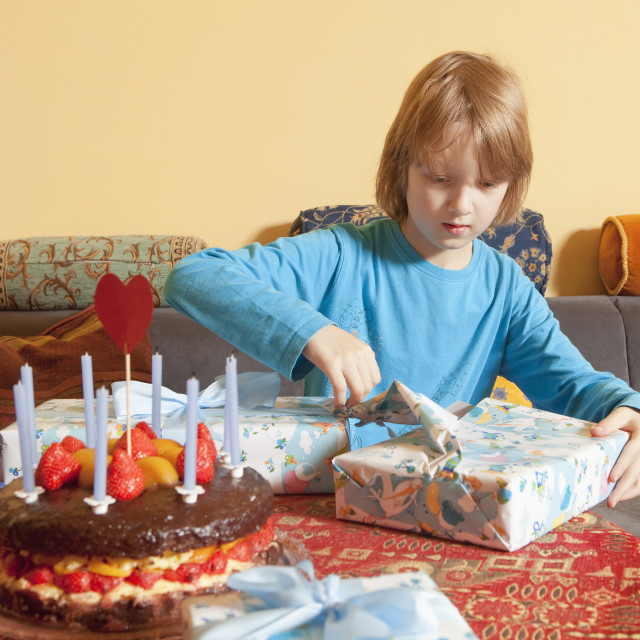 """""""Boy with Blond Hair Opening his Birthday Presents"""" stock image"""